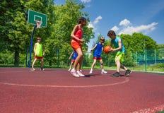 Los muchachos y la muchacha juegan al juego de baloncesto en patio Imagenes de archivo