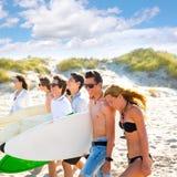 Los muchachos y las muchachas adolescentes de la persona que practica surf agrupan caminar en la playa Fotografía de archivo libre de regalías