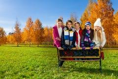 Los muchachos y las muchachas adolescentes se colocan en el banco Imagen de archivo