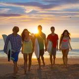 Los muchachos y las muchachas de las personas que practica surf agrupan caminar en la playa Imagenes de archivo