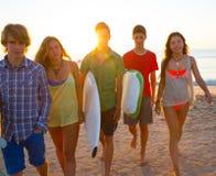 Los muchachos y las muchachas de las personas que practica surf agrupan caminar en la playa Foto de archivo libre de regalías