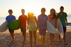 Los muchachos y las muchachas de las personas que practica surf agrupan caminar en la playa Fotos de archivo libres de regalías