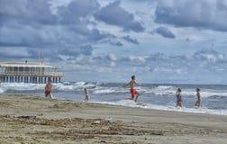 Los muchachos y las muchachas en un viaje de escuela se divierten en el mar Imagenes de archivo