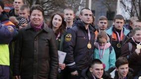 Los muchachos y las muchachas jovenes en uniforme del rescate con las medallas presentan para la foto en la calle almacen de metraje de vídeo