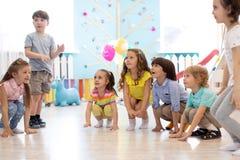 Los muchachos y las muchachas preescolares de los ni?os se ponen en cuclillas jugar en guarder?a foto de archivo