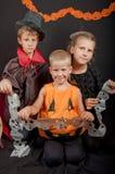 Los muchachos y los disfraces de Halloween que llevan de la muchacha Foto de archivo