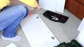 Los muebles blancos de junta de la mujer, ella aprieta un tornillo con un destornillador almacen de metraje de vídeo