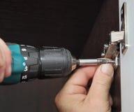 Los muebles de junta, carpintero instalan el guardarropa de las bisagras de puerta, u Foto de archivo libre de regalías
