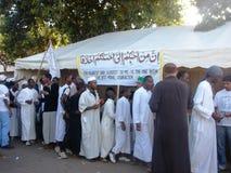 Los musulmanes pasan por una tienda en un lado del camino Imagen de archivo