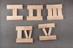 Los números romanos hechos de bloques de madera del juguete mintieron en fondo gris de la tela Fotos de archivo