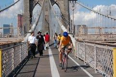 Los neoyorquinos recorren en el puente de Brooklyn Imagen de archivo libre de regalías
