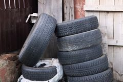 Los neumáticos de goma viejos mienten aleatoriamente cerca de una casa de madera abandonada fotos de archivo libres de regalías