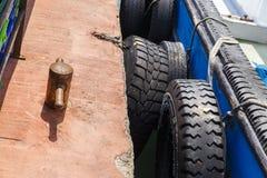 Los neumáticos a bordo de una nave amarraron en el muelle Fotos de archivo