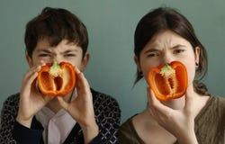 Los niños adolescentes con el dulce rojo cortaron la pimienta búlgara de la paprika Fotos de archivo