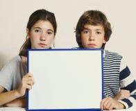 Los niños adolescentes muchacho y muchacha sostienen la hoja del papel en blanco Fotos de archivo libres de regalías