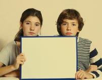 Los niños adolescentes muchacho y muchacha sostienen la hoja del papel en blanco Foto de archivo
