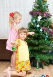 Los niños adornan el árbol de navidad Imagenes de archivo