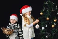 Los niños adornan el árbol de navidad en el cuarto Fotografía de archivo libre de regalías