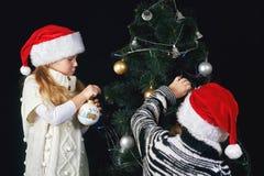 Los niños adornan el árbol de navidad en el cuarto Foto de archivo libre de regalías
