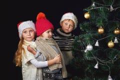 Los niños adornan el árbol de navidad en el cuarto Fotos de archivo