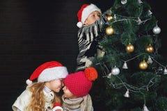 Los niños adornan el árbol de navidad en el cuarto Fotos de archivo libres de regalías