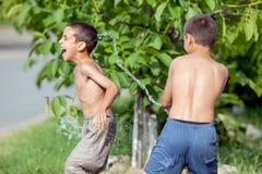 Los niños afuera en un día de verano, rociado con los globos llenaron w fotografía de archivo libre de regalías
