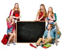 Los niños agrupan con el anuncio en la pizarra en blanco de la escuela fotografía de archivo