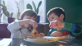Los niños alegría, los niños hambrientos comen los alimentos de preparación rápida durante cena en restaurante de la pizzería en  almacen de metraje de vídeo
