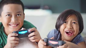 Los niños alegres están jugando la videoconsola metrajes