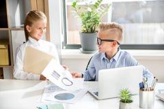 Los niños alegres responsables están analizando datos en oficina Imagen de archivo