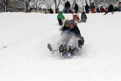 Los niños alegres sledding abajo Foto de archivo