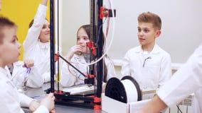 Los niños alrededor de la impresora 3D estudian tecnología moderna almacen de video