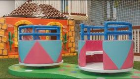 Los niños alrededor del carrusel dan vuelta en el área de juego Subidas de la niña en él almacen de video