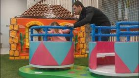 Los niños alrededor del carrusel dan vuelta en el área de juego Subidas de la niña en él El papá rueda a su hija almacen de video