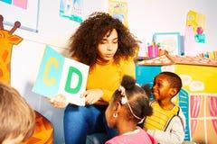 Los niños aprenden alfabeto en guardería con el profesor imagen de archivo