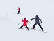 Los niños aprenden esquiar con un coche en las montañas Fotos de archivo libres de regalías