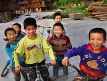Los niños asiáticos divertidos de las zonas rurales de China, paseo bikes. Foto de archivo