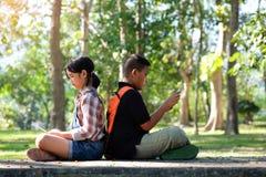 Los niños asiáticos están jugando una tableta en el parque Foto de archivo libre de regalías