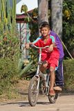 Los niños asiáticos están montando la bicicleta foto de archivo
