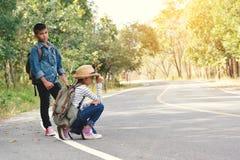 Los niños asiáticos felices hacen excursionismo en el fondo del camino y del bosque Imagenes de archivo