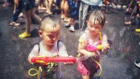 Los niños asperjan el agua en el festival de Songkran foto de archivo
