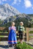 Los niños bávaros de Smilling en una montaña hermosa ajardinan Imagen de archivo