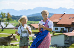 Los niños bávaros felices beben la leche en el prado con la vaca montan@as Foto de archivo libre de regalías