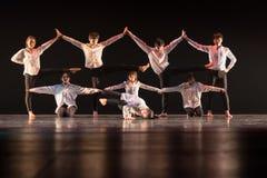 Los niños bailan para conectar la ropa negra del blanco de la etapa Foto de archivo