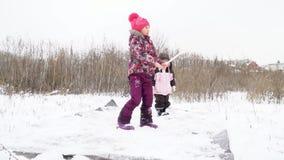 Los niños batieron hacia fuera la estera en invierno almacen de video