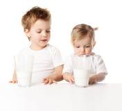 Los niños beben la leche, aislada en el fondo blanco Imagenes de archivo