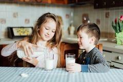 Los niños beben la leche en la cocina en la mañana imagen de archivo