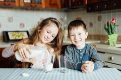 Los niños beben la leche en la cocina en la mañana fotos de archivo