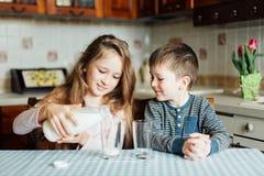 Los niños beben la leche en la cocina en la mañana La hermana vierte la leche en un vidrio imagenes de archivo