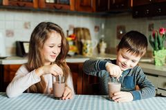 Los niños beben la leche y se divierten en la cocina en la mañana La hermana y el hermano preparan el cacao imagen de archivo libre de regalías